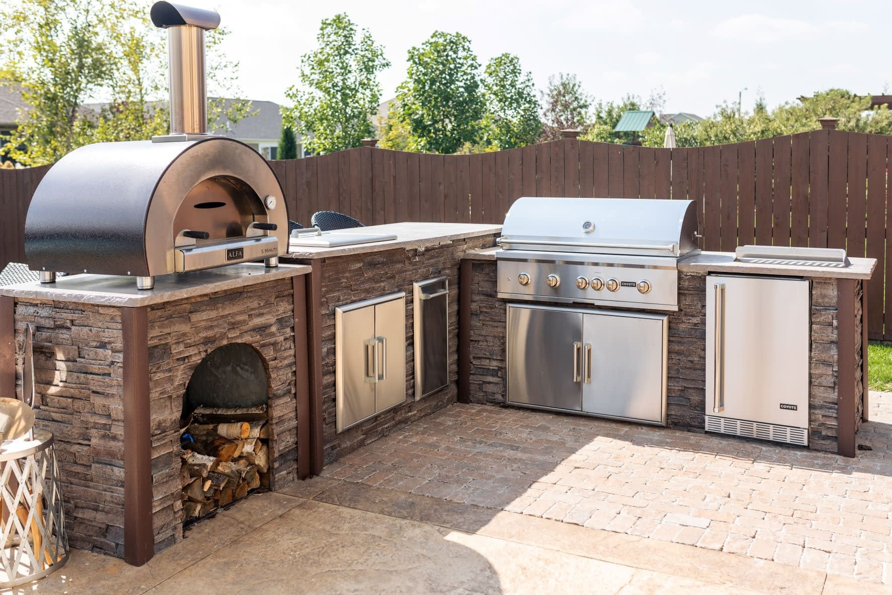 custom l-shape outdoor kitchen with built in pizza oven
