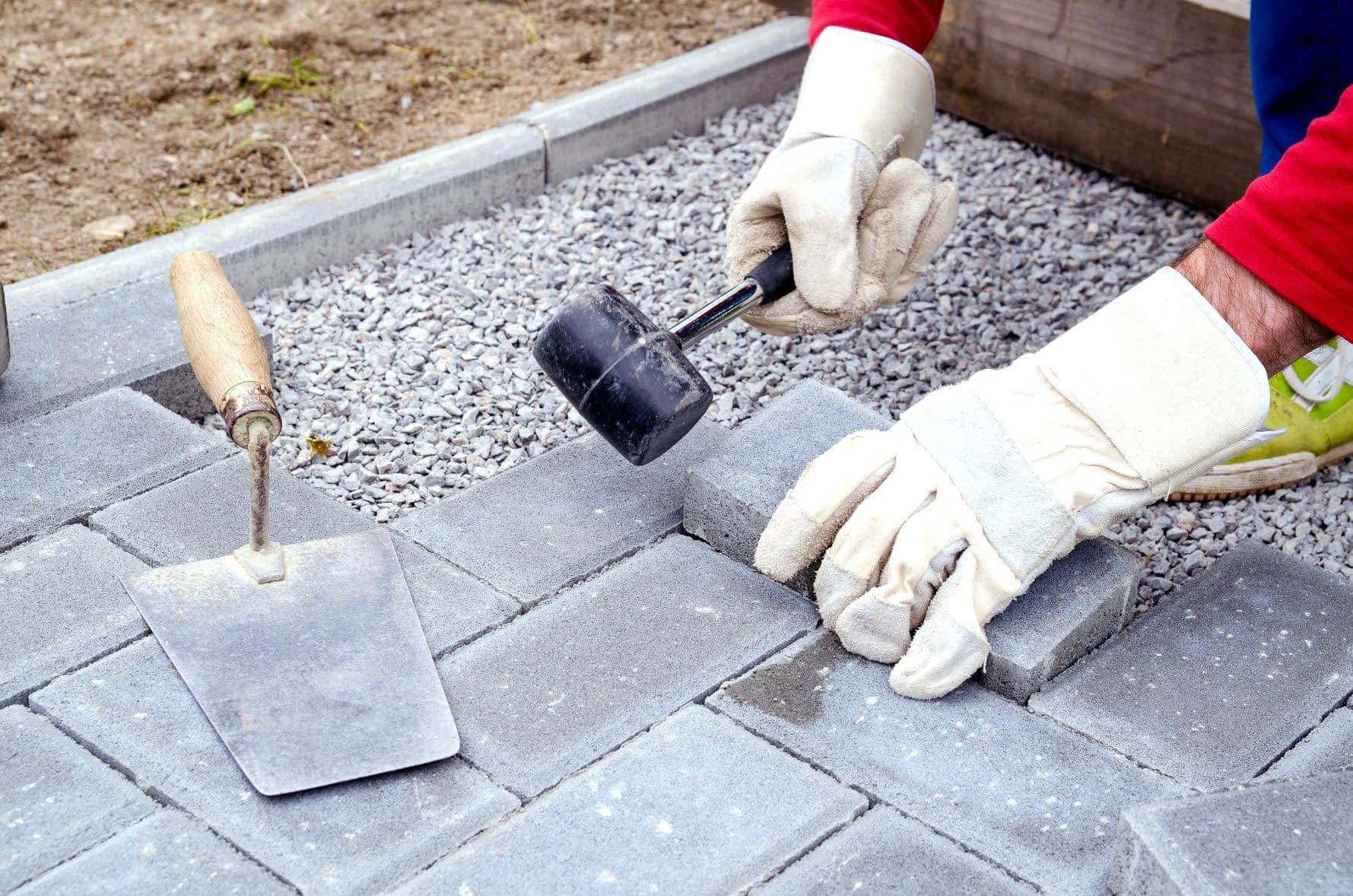 contractor laying paver patio surface for outdoor kitchen