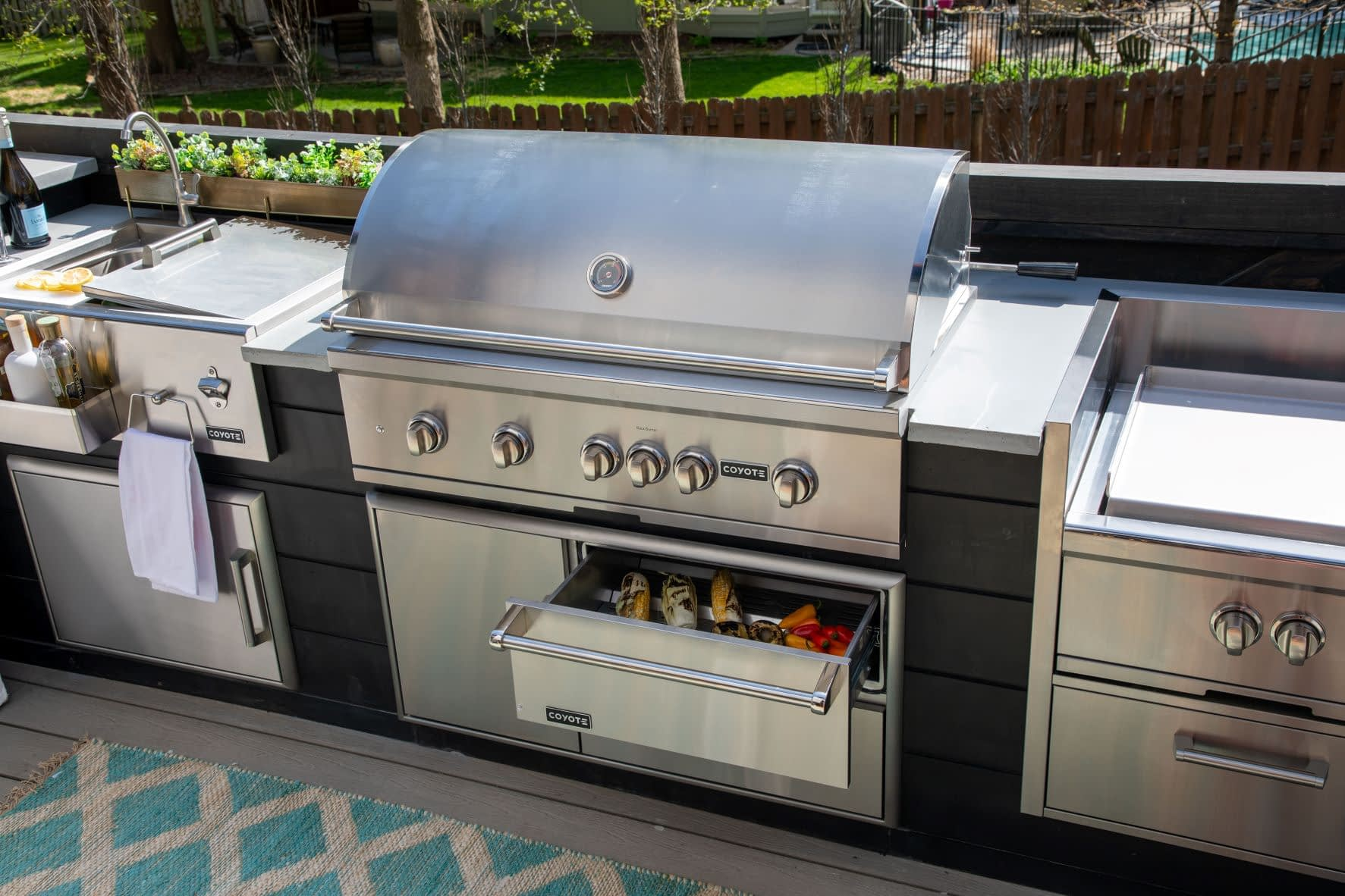 l-shape outdoor kitchen with open warming drawer