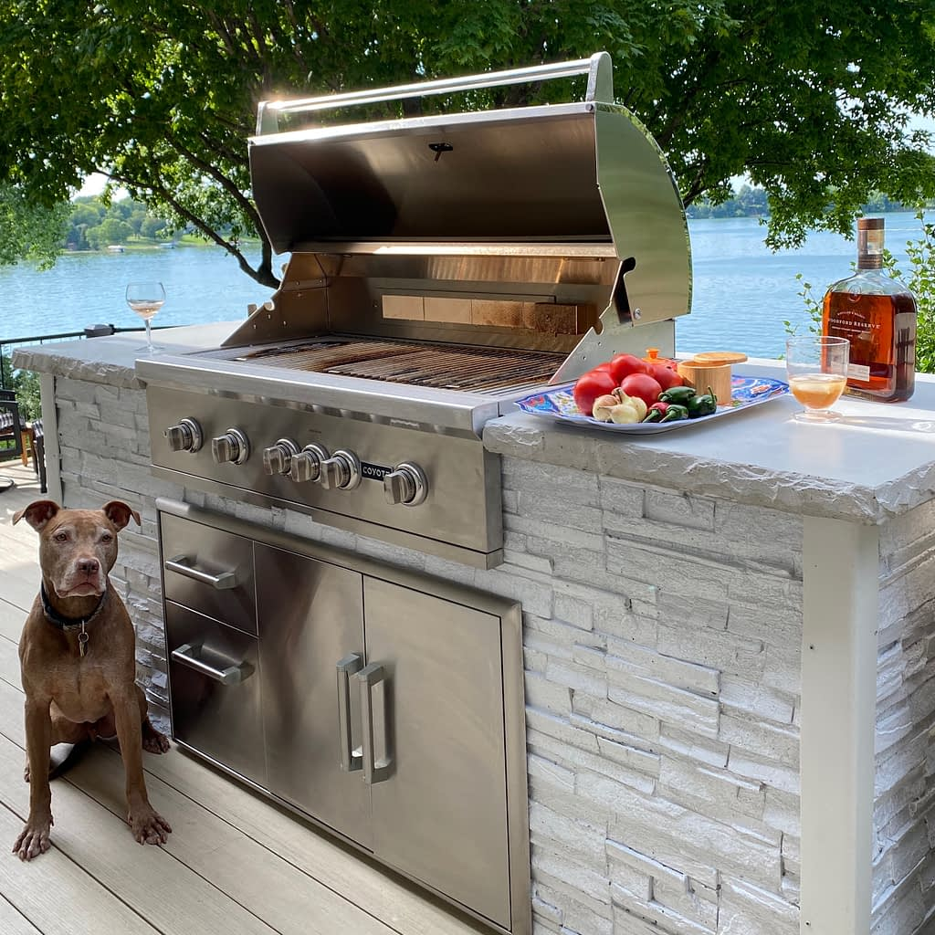 outdoor kitchen on deck near water with dog